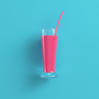 Glass with pink cocktail and straw on bright blue background