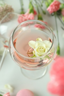 Glass with pink wine and flower, close up