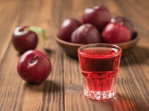 熟した梅とボウルの表面に梅アルコールとガラス