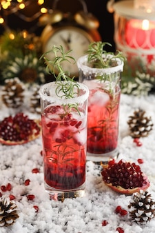 크리스마스 파티를 위한 설탕에 절인 크랜베리 로즈마리 칵테일을 곁들인 석류 마가리타와 유리