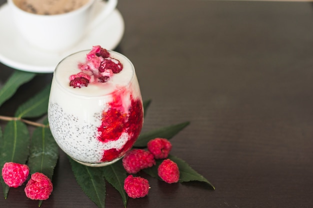 Glass with raspberries; chia seeds and yogurt on green leaves over black background