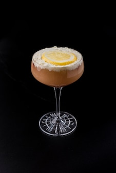 Glass with red cocktail with cream and orange slice on black background
