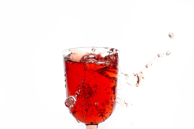 Glass with red drink on a white background copy space