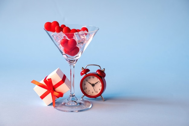 Glass with red heart shaped sugar candy and ice. gift box and red alarm clock on a blue background. time for love.valentines day, anniversary or wedding celebration concept. copy space.