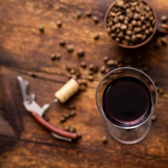 갈색 오래 된 나무 배경에 레드 와인과 커피 콩 유리.