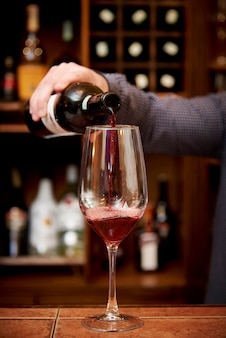 In a glass with red wine the barman pours wine from a bottle