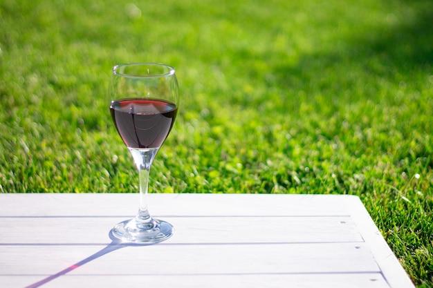 잔디 배경에 흰색 나무 테이블에 레드 와인과 유리. 복사 공간