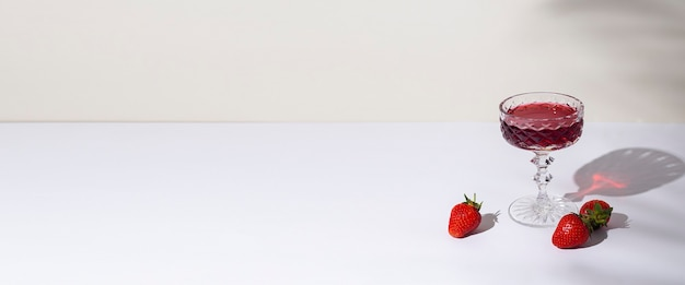 Glass with red wine and strawberries on the table on a light background. top view, flat lay. banner.
