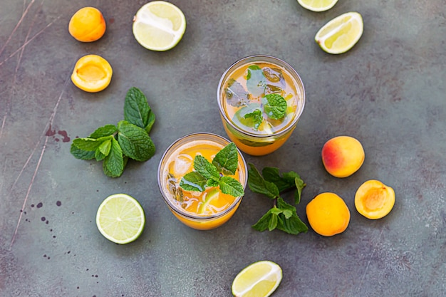 Glass with refreshment mocktail with apricot, mint and lime. cold cocktail or iced tea.