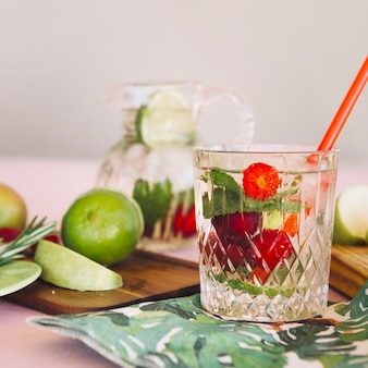 Glass with strawberries infused water near fruits on chopping board