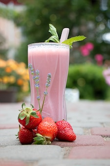 Glass with strawberry smoothie and strawberries on the path in the garden
