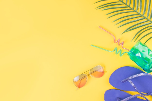 Glass with straws near sunglasses with flip flops and plant leaf