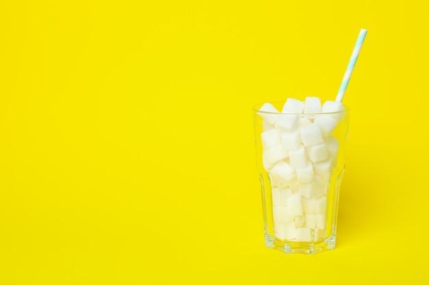 Стекло с кубиками сахара и соломкой на желтой поверхности