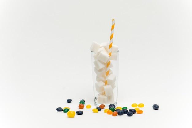 Стакан с сахаром с соломкой конфеты драже сладости калорийность