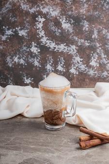 대리석 표면에 맛있는 음료와 계피가 들어간 유리.