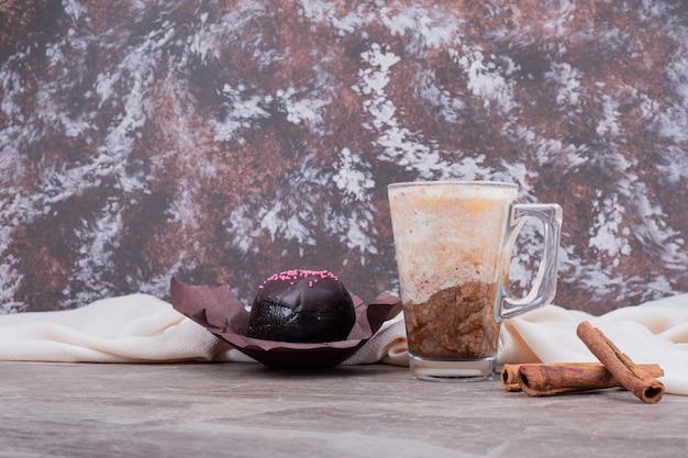대리석에 맛있는 음료와 계피가 들어간 유리.