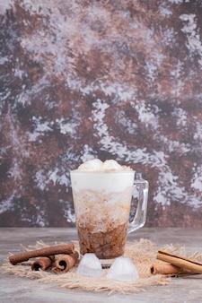 Vetro con gustosa bevanda e cannella sulla superficie in marmo.