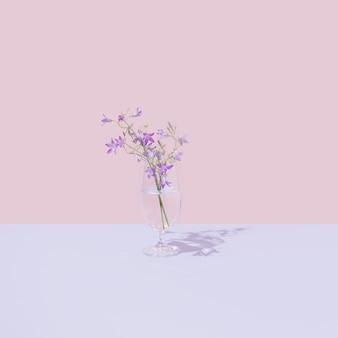 투명한 액체와 아름다운 보라색 들판 꽃이 있는 유리. 밝은 파스텔 핑크 배경. 최소한의 자연 미학.