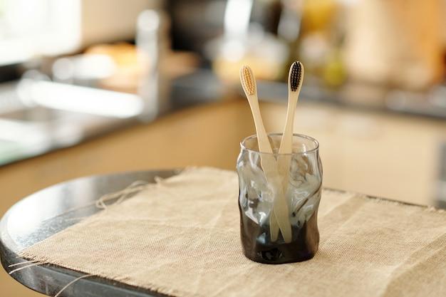 Стакан с двумя экологически чистыми зубными щетками из бамбука на столе, покрытом льняной тканью