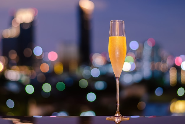A glass with vapour of cold champagne on table with colorful city bokeh lights background