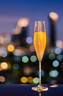 A glass with vapour of cold champagne on table with colorful city bokeh lights