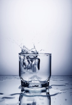 Glass with vodka, alcohol, water on a gray background with pieces of ice falling to it with splashes