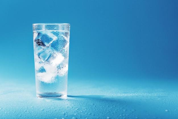 青い背景に水と角氷とガラス。暑い蒸し暑い日に救助のコンセプト。フリースペース