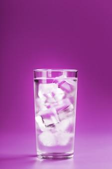 ピンクの背景に水と角氷とガラス