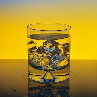 노란색 배경에 물과 얼음 유리
