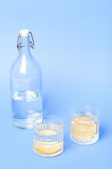 青い表面のボトルの近くに水とレモンのガラス