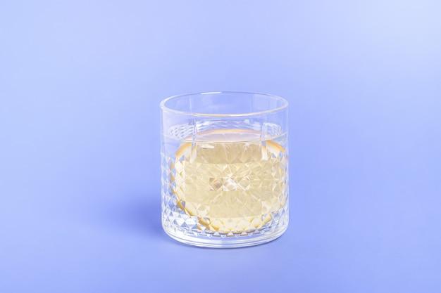 青い表面に水とレモンのガラス