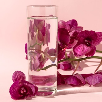 Glass with water next to flowers