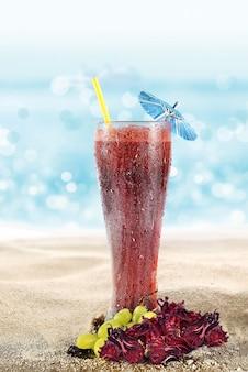 해변의 모래에 자메이카의 물과 포도가 든 유리