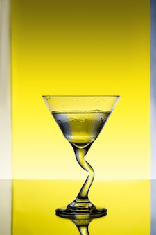 Glass with water over grey and yellow background.