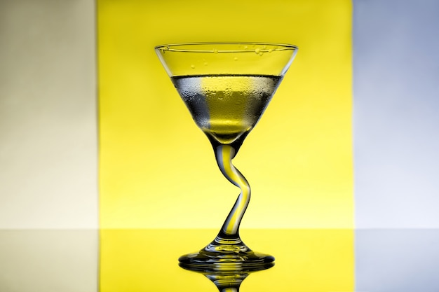 Glass with water over grey and yellow surface