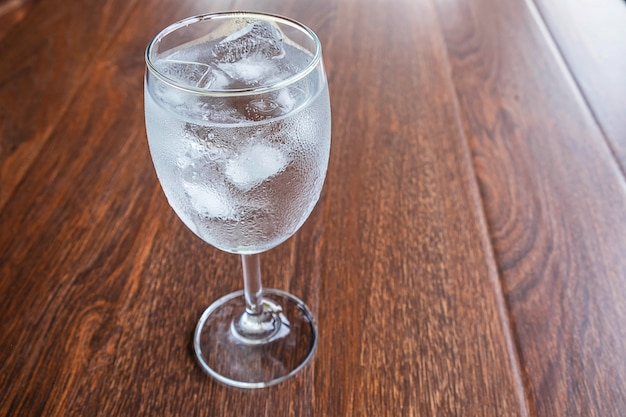 Glass with water and ice on the table