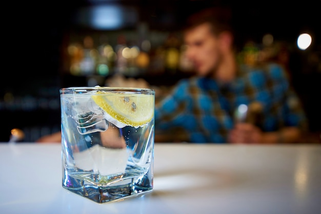 A glass with water, lemon and ice on the bar.