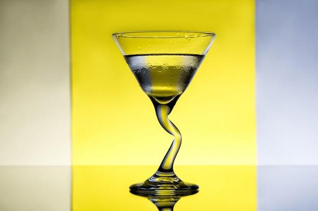 Стакан с водой над серой и желтой поверхностью