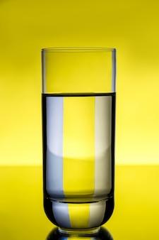 黄色の壁の上の水とガラス