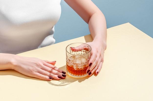 파란색 배경에 테이블에 여자 손에 위스키와 아이스 큐브 유리. 현대 아이소 메트릭 스타일. 창의적인 개념