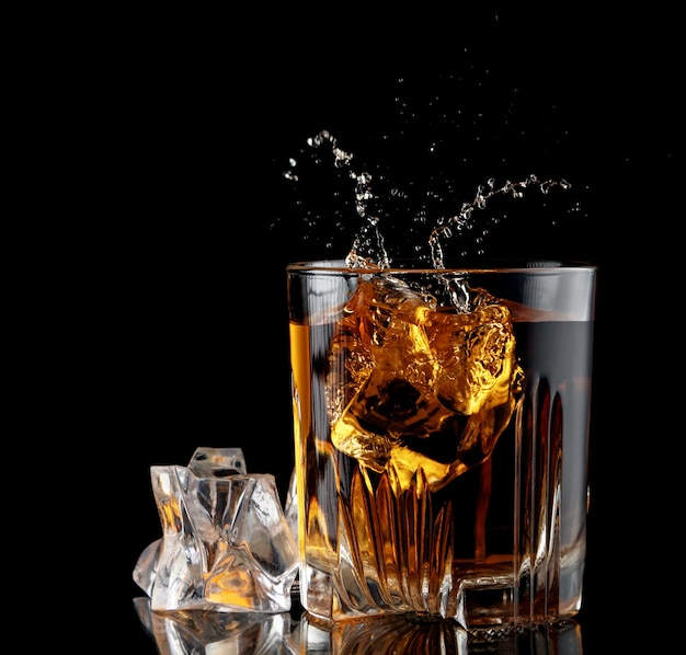 Glass with whiskey and falling ice cube with splashes