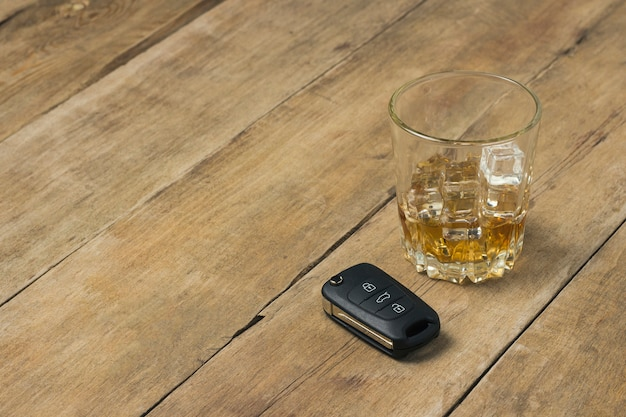 Glass with whiskey and ice and car keys on a wooden background. drunk driving concept, the risk of drinking and driving, alcohol intoxication.