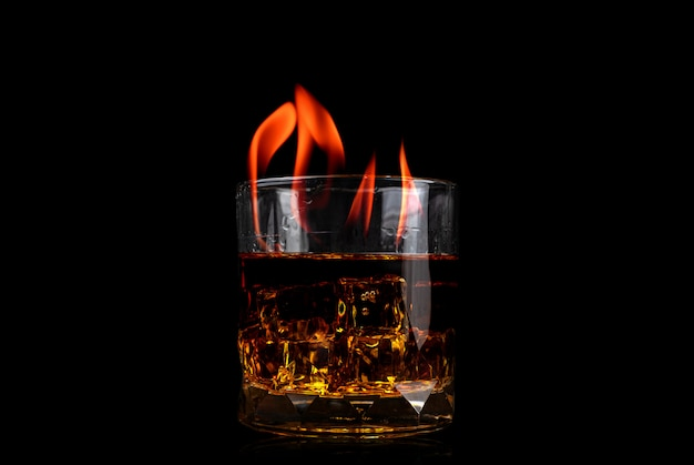 Glass with whiskey of ice cube and fire flame on black background