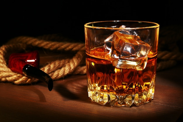 Glass with whiskey, ice cubes and smoking pipe.