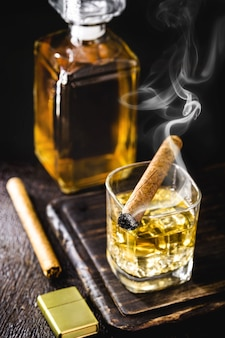 Glass with whiskey and ice tongs with cigar on wooden table