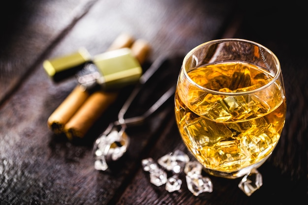 Glass with whiskey and ice tongs on wooden table