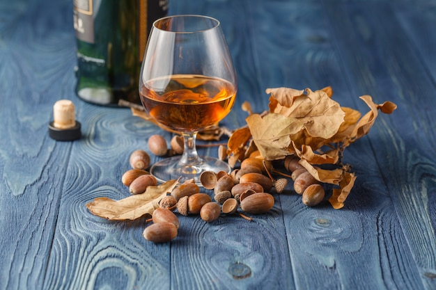 Glass with whiskey on wooden table