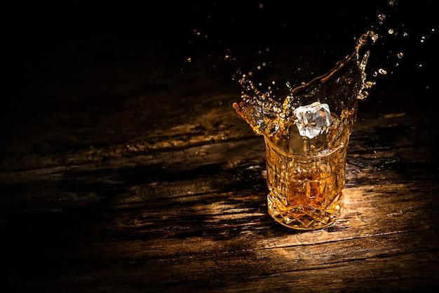 Стакан с виски, коньяком или другим алкоголем с брызгами кубика льда на деревянном фоне