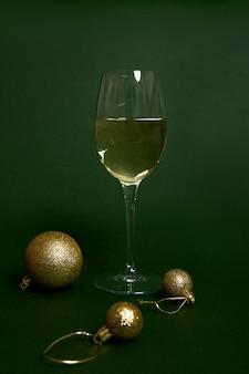 Стекло с белым вином на зеленом фоне с золотыми сферическими елочными украшениями, елочными шарами. новогодний концептуальный снимок с мягкой тенью в монохромном и двухцветном стиле для дизайна и рекламы