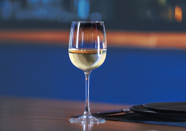 Glass with white wine on table